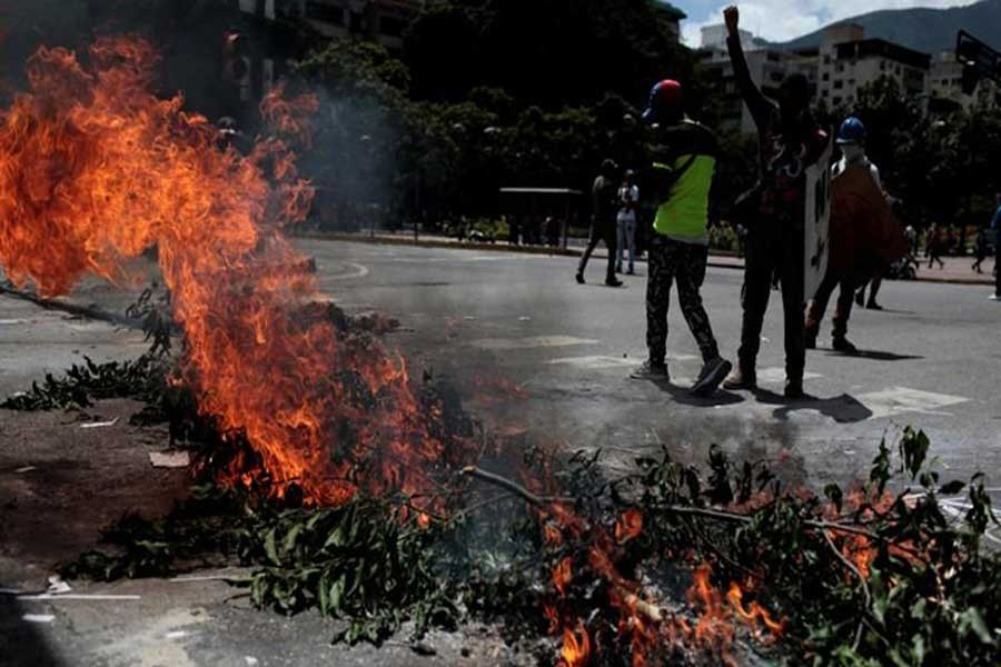Demonstrators block a street at a rally against Venezuela's President Nicolas Maduro's government in Caracas, Venezuela on Wednesday.