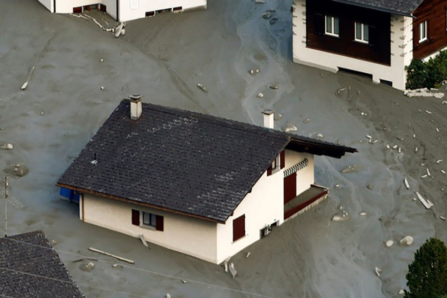 A house is surrounded by debris of a landslide in the village of Bondo on Saturday.