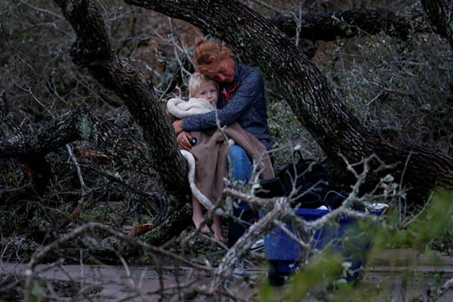 Lisa Rehr holds her four-year old son Maximus, after they lost their home to Hurricane Harvey, as they await to be evacuated with their belongings from Rockport, Texas, US August 26, 2017. Reuters