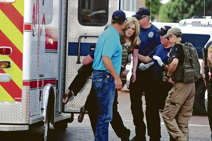 An injured woman is carried to an ambulance in Clovis, New Mexico on Monday, as authorities respond to reports of a shooting inside a public library. - AP photo