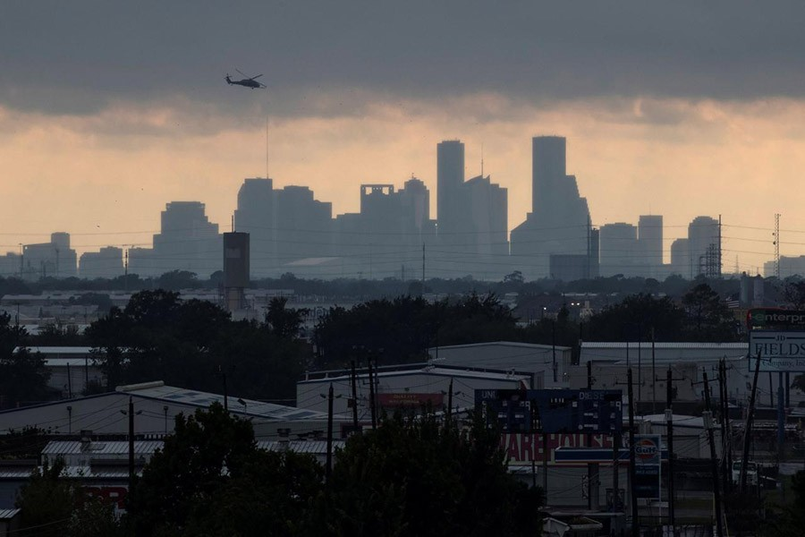 A helicopter hovers above the Houston skyline as sunlight breaks through storm clouds from Tropical Storm Harvey in Texas, US on Tuesday. - Reuters photo