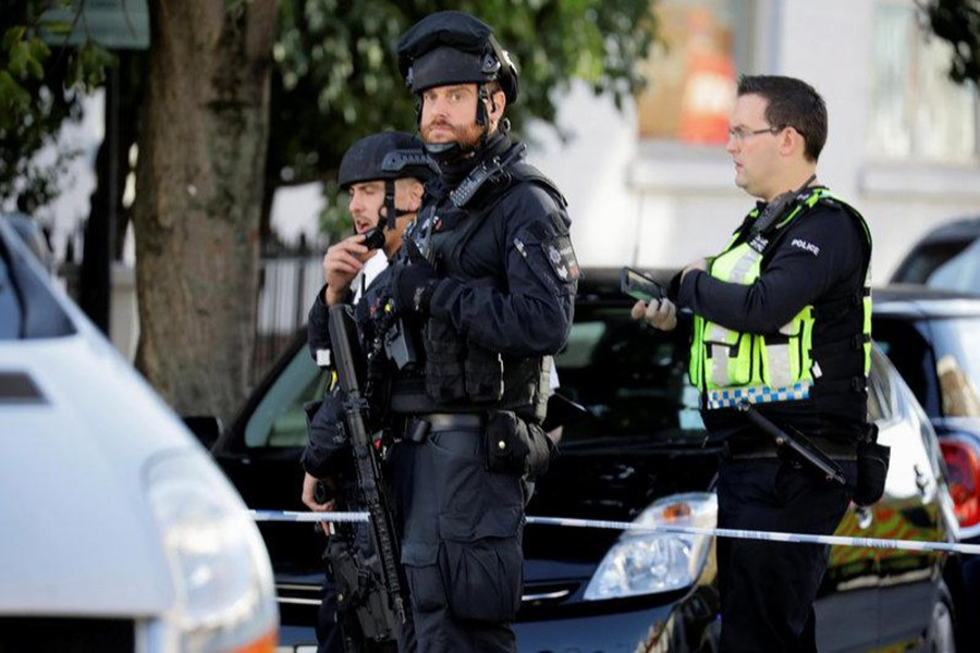 Armed policemen stand by cordon outside Parsons Green tube station in London, Britain on Friday. - Reuters