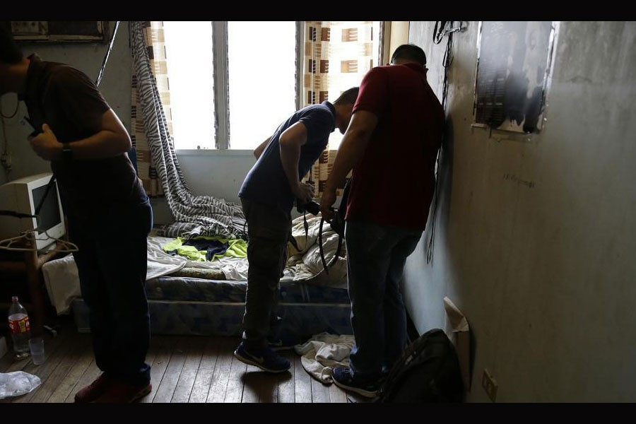 In this April 20, 2017, photo, investigators check a room in the home of suspected child webcam cybersex operator, David Timothy Deakin, from Peoria, Ill., during a raid in Mabalacat, Philippines.(AP Photo)
