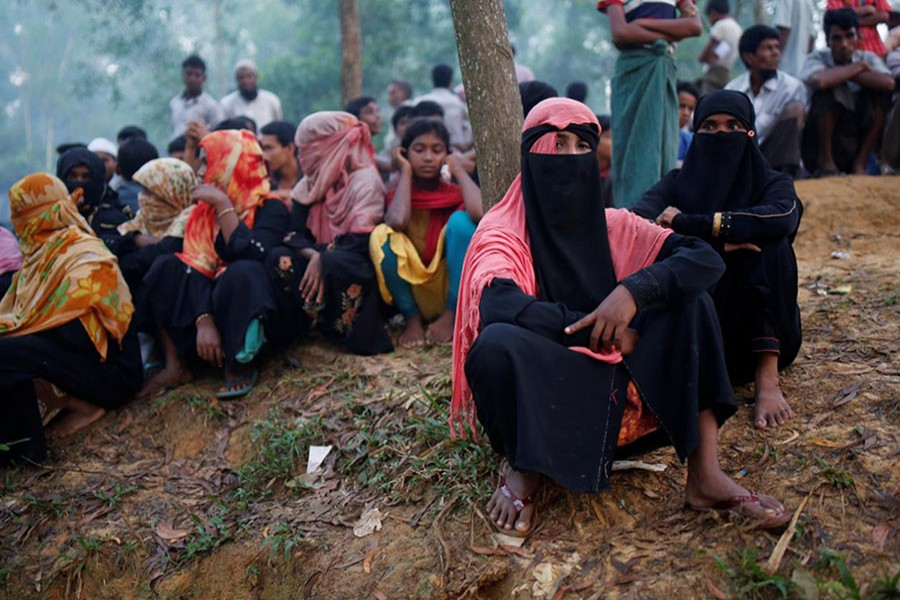 Rohingya refugees wait to receive humanitarian aid at Kutupalong refugee camp near Cox's Bazar on Tuesday. - Reuters photo
