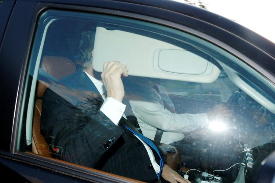 Former Trump campaign manager Paul Manafort hides behind his car visor as he leaves his home in Alexandria, Virginia on Monday. -Reuters Photo
