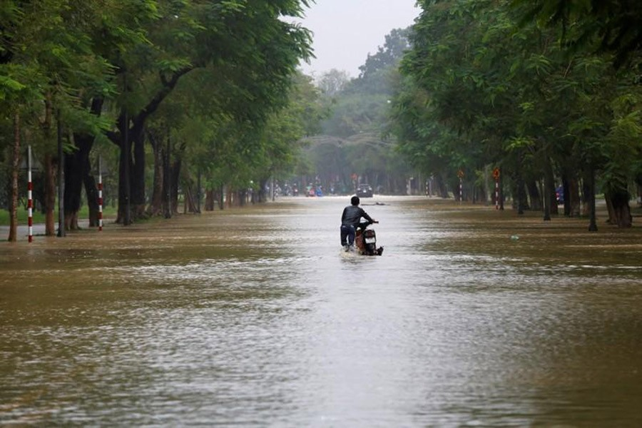 A man pushes his motorcycle along flooded road after typhoon Damrey hits Vietnam in Hue city, Vietnam on Sunday. - Reuters photo