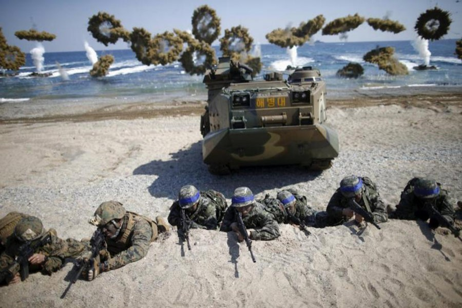 South Korean (blue headbands) and US Marines take positions during a US-South Korea joint landing operation drill in Pohang, South Korea on March 12, 2016. - Reuters file photo
