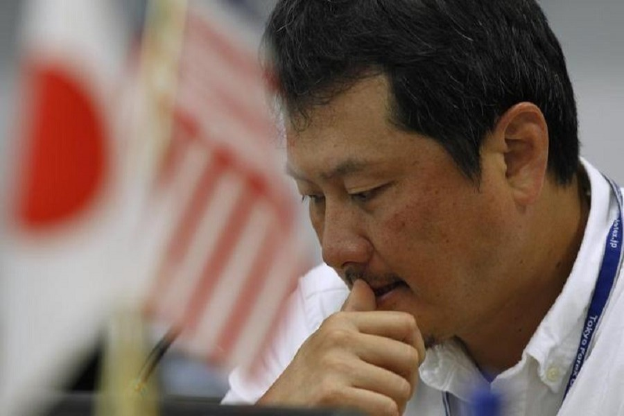 A foreign exchange broker rests his thumb on his lips as he is pictured near Japanese and American flags at a trading room in Tokyo October 26, 2011. Reuters/Files