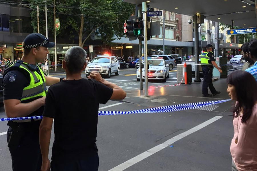 Police officers stand guard as members of the public stand behind police tape after the arrest of the driver of a vehicle that ploughed into pedestrians at a crowded intersection in central Melbourne, Australia on Thursday. - Reuters photo