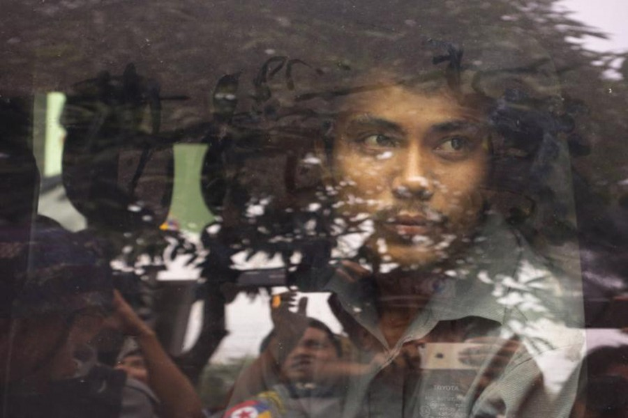 Reuters reporter Kyaw Soe Oo looks out from a police vehicle as he leaves a court in Yangon, Myanmar on Wednesday. - Reuters photo
