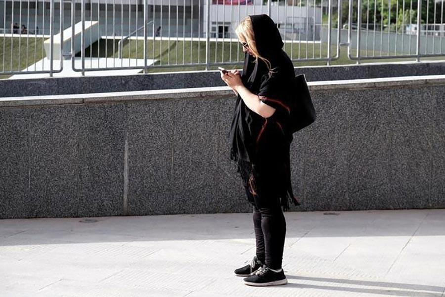 An Iranian woman uses her mobile phone at a park in Tehran, Iran. -Reuters Photo