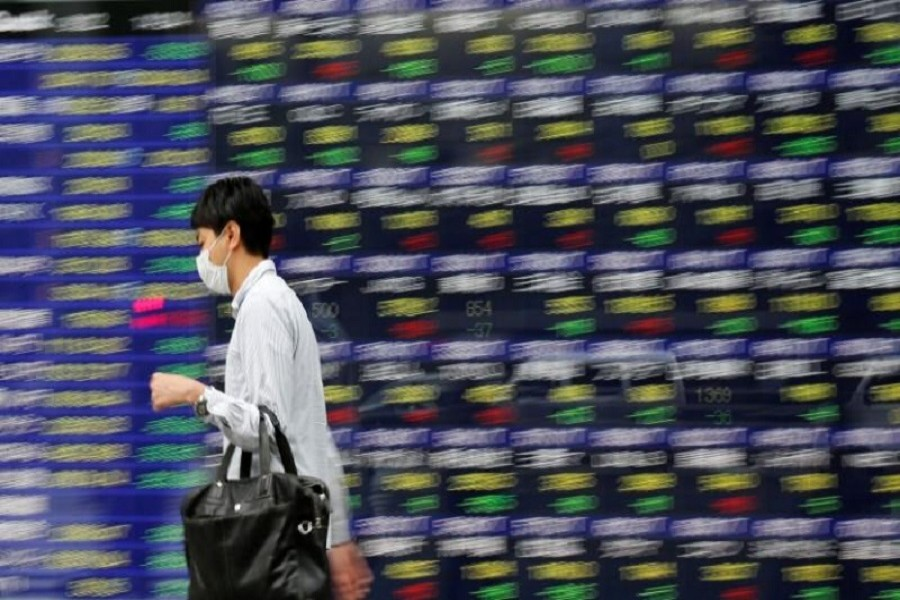 People walk past an electronic stock quotation board outside a brokerage in Tokyo, Japan, September 22, 2017. Reuters/File Photo