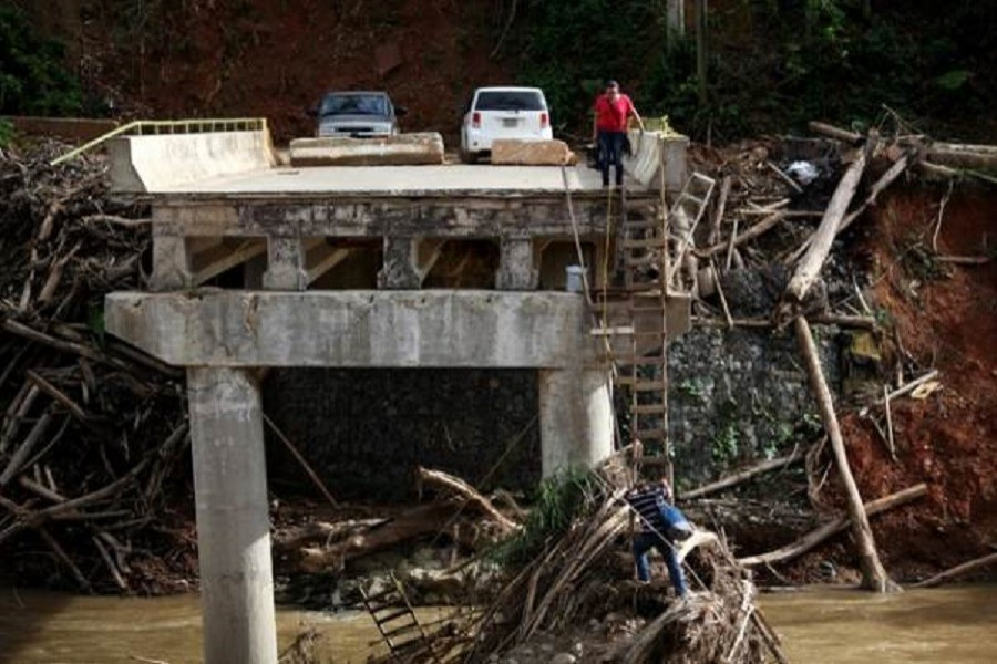 A woman looks as her husband climbs down a ladder at a partially destroyed bridge, after Hurricane Maria hit the area in September, in Utuado, Puerto Rico November 9, 2017. Reuters/Files