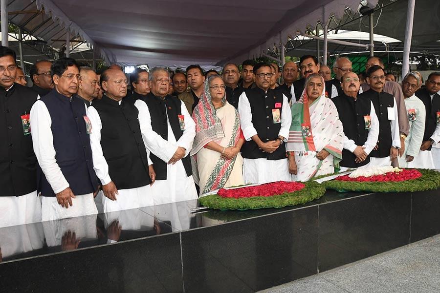 Prime Minister Sheikh Hasina is standing in solemn silence, flanked by central Awami League leaders, after placing wreath at portrait of Bangabandhu in front at Dhanmondi on Monday marking National Independence Day. -Focus Bangla Photo