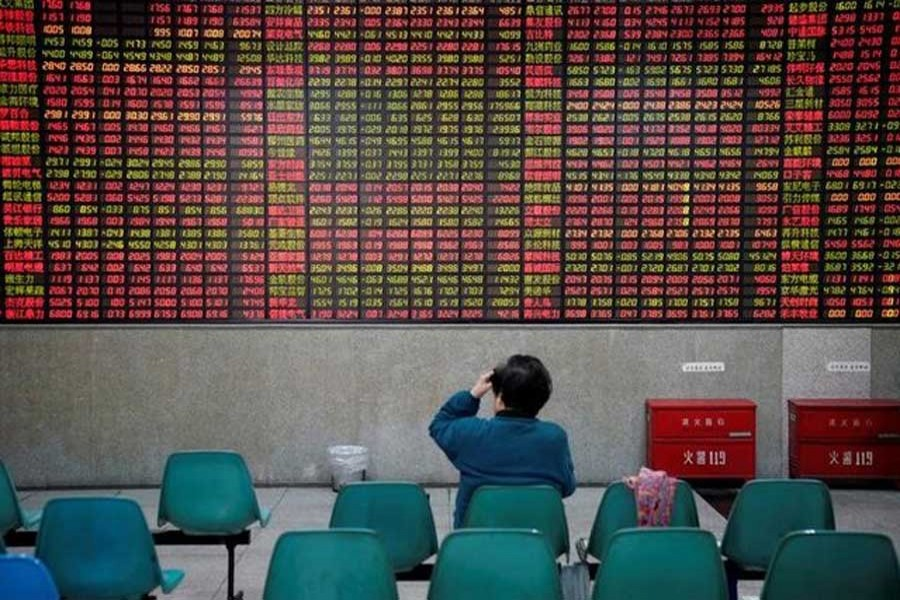 An investor looks at an electronic board showing stock information at a brokerage house in Shanghai, China November 24, 2017. Reuters/File Photo