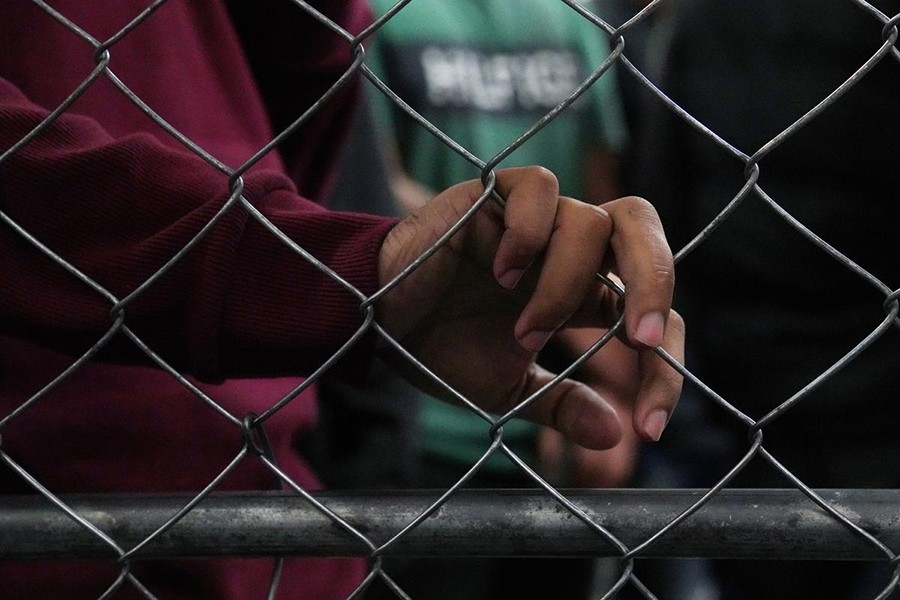 Single-adult male detainees wait along a fence inside a Border Patrol station in McAllen, Texas, US on July 12, 2019 — Reuters photo