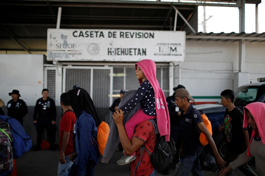 People belonging to a caravan of migrants from Honduras en route to the United States walk by an immigration checkpoint in Huehuetan, Mexico on April 15, 2019 — Reuters/Files