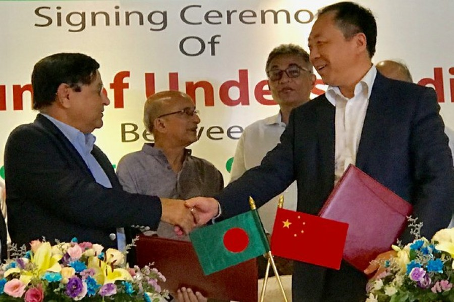 A.M. Khurshed Alam, chief executive officer of the NWPGC, shakes hands with Ruan Guang, chairman of the CMC, after they signed a MoU on implementing the renewable energy projects. (Photo- collected)