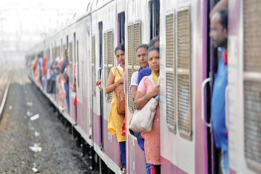 Women commuters travel by a suburban train as they head toward their destination in Mumbai, July 5, 2019. Reuters/Files