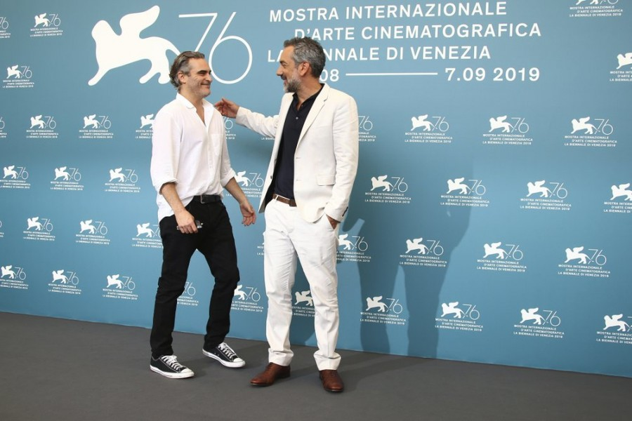 Actor Joaquin Phoenix, left, greets director Todd Phillips at the photo call for the film 'Joker' at the 76th edition of the Venice Film Festival in Venice, Italy, Saturday, Aug. 31, 2019. (Photo by Joel C Ryan/Invision/AP)