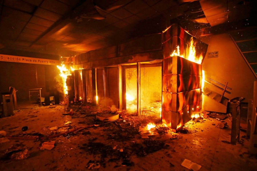 A subway ticket office is seen on fire during a protest against the increase in the subway ticket prices in Santiago, Chile, October 19, 2019 REUTERS/Ramon Monroy