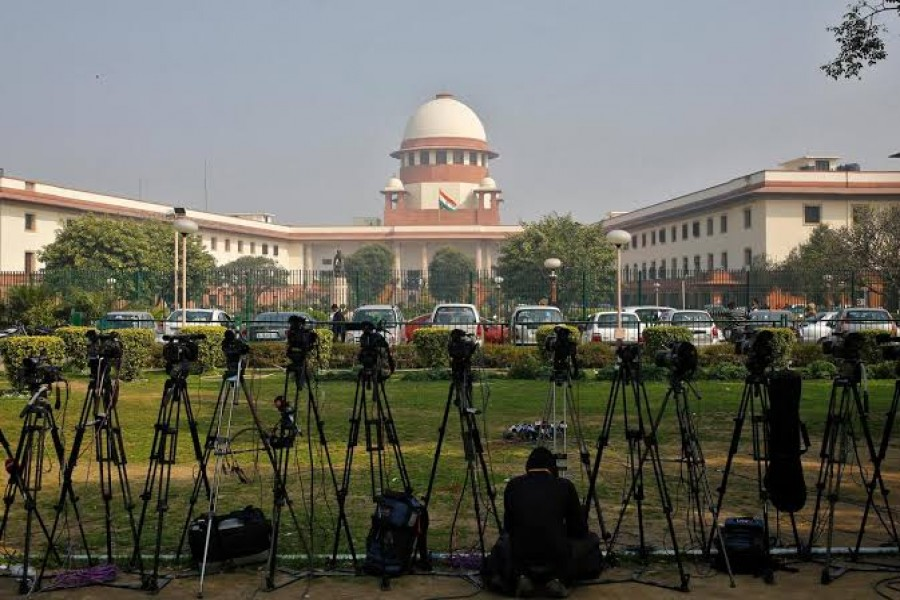 A television journalist sets his camera inside the premises of the Supreme Court in New Delhi, February 18, 2014. Reuters/File Photo