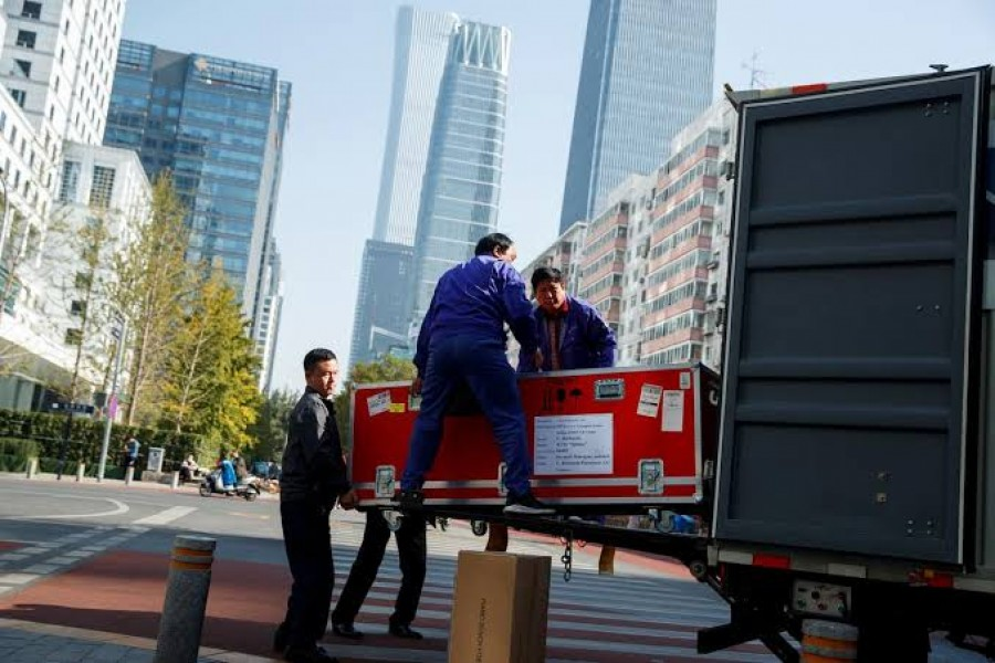 Men unload cargo from the truck of a logistics firm in Central Business District in Beijing, China October 29, 2019. Picture taken October 29, 2019. REUTERS/Thomas Peter
