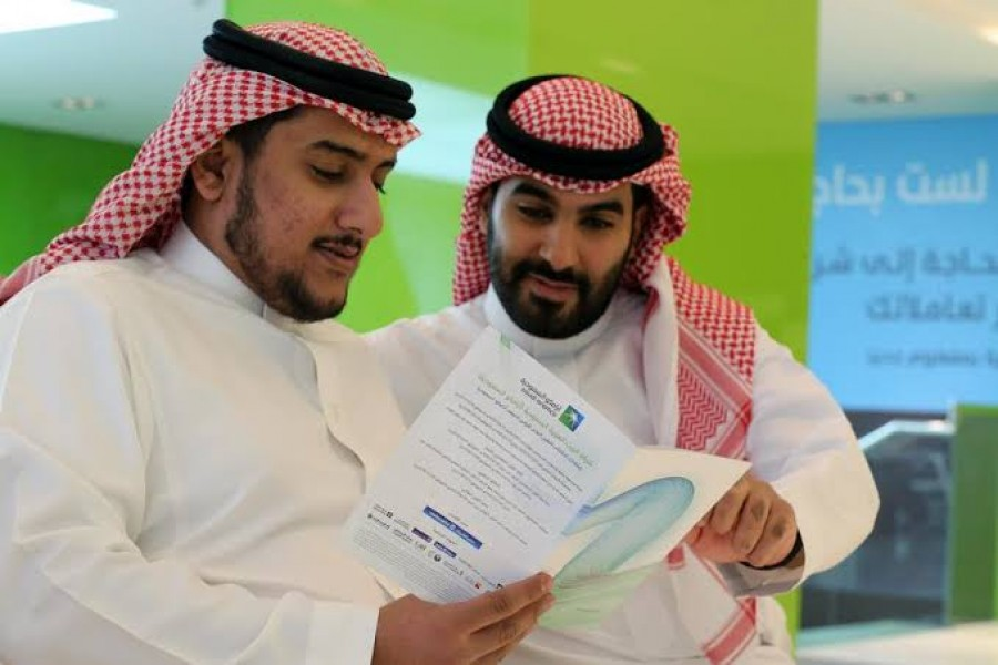 Saudi men check the prospectus of Aramco IPO, in Riyadh, Saudi Arabia, November 17, 2019. Reuters