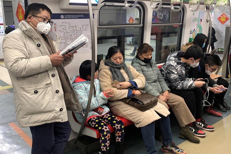 A man wearing a mask reads on the subway in Beijing, China on January 21, 2020 — Reuters photo