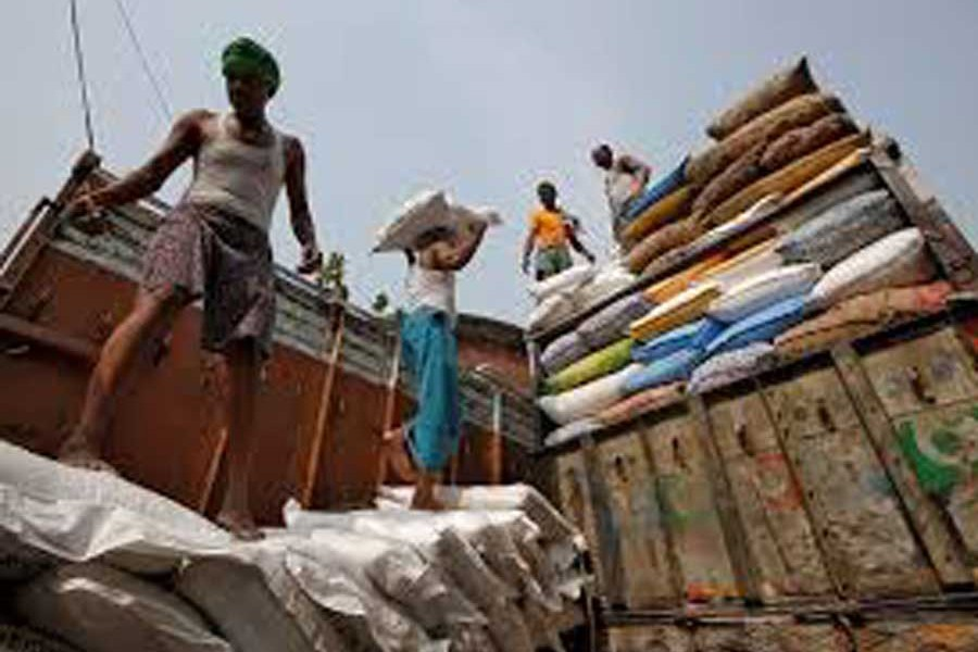 A labourer carries a sack filled with sugar to load it onto a supply truck at a wholesale market in Kolkata, India	— Reuters