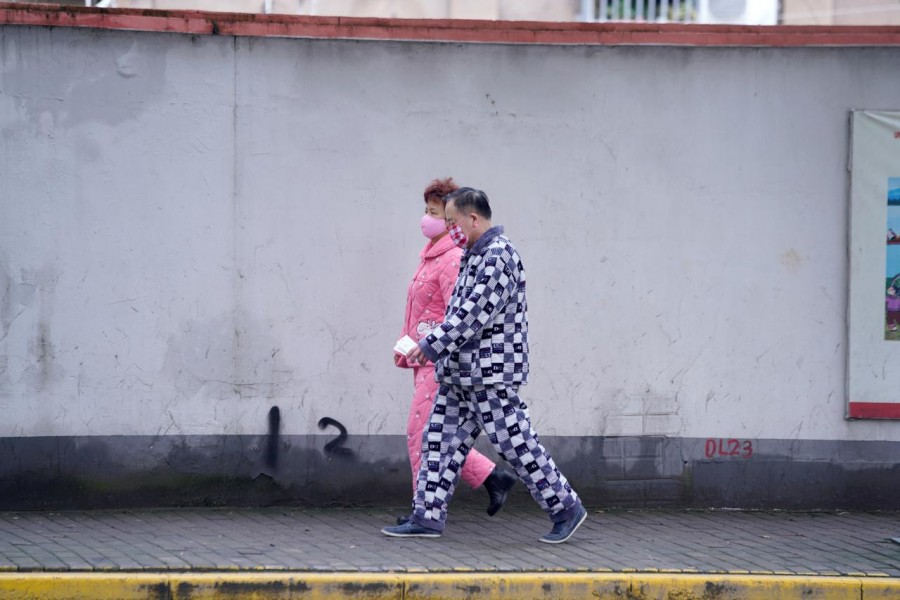 Residents wearing face masks and pyjamas are seen on a street in Shanghai, China, as the country is hit by an outbreak of the novel coronavirus, February 14, 2020. Reuters