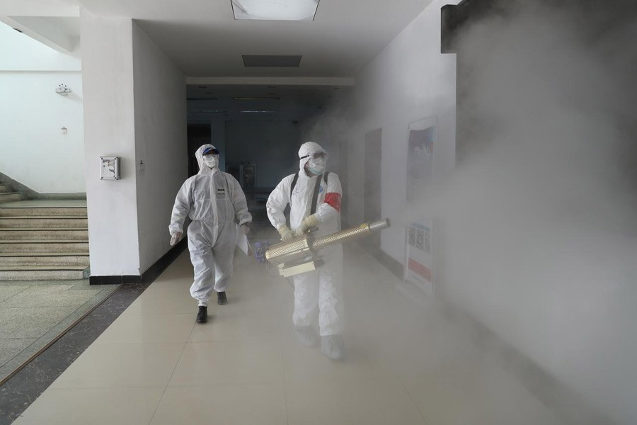 Volunteers in protective suits disinfect a residential compound in Wuhan, the epicentre of the novel coronavirus outbreak, in Hubei province, China, February 22, 2020. China Daily via Reuters