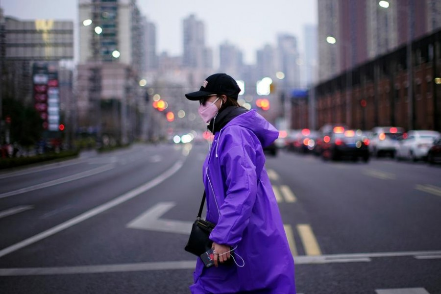 A woman wearing a face mask is seen on a street in downtown Shanghai, China, as the country is hit by an outbreak of a new coronavirus, February 26, 2020 — Reuters