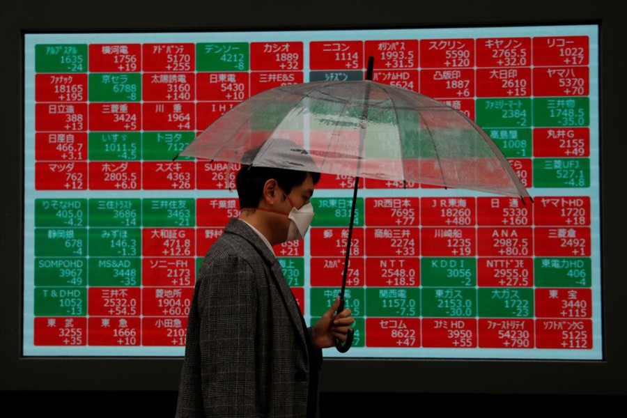 A visitor wearing protective face mask, following an outbreak of the coronavirus, walks past in front of a stock quotation board outside a brokerage in Tokyo, Japan, March 02, 2020 — Reuters