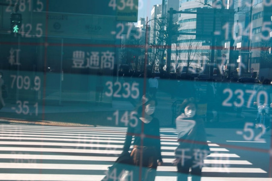 People wearing protective face masks, following an outbreak of the coronavirus, are reflected on a screen showing Nikkei index, outside a brokerage in Tokyo, Japan, February 28, 2020 — Reuters/Files