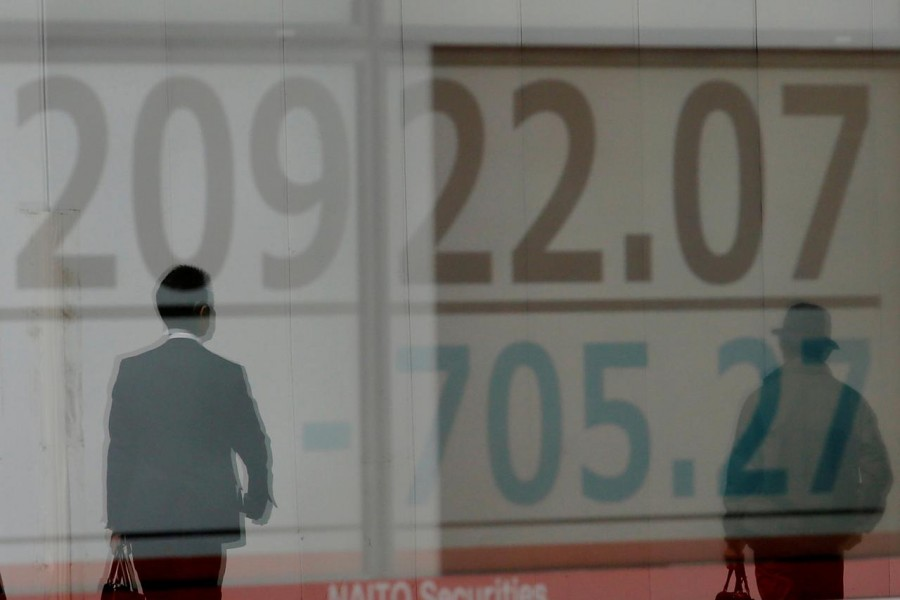 Men are reflected on an electronic board showing the Nikkei stock index outside a brokerage in Tokyo, Japan, March 25, 2019 — Reuters/Files