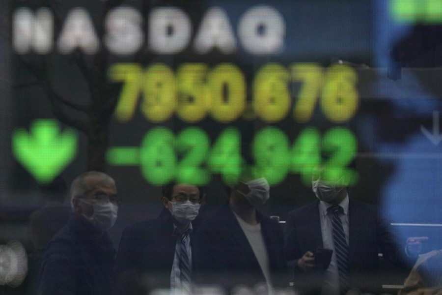 People wearing protective face masks, following an outbreak of the coronavirus disease (COVID-19), are reflected in a screen displaying NASDAQ movements outside a brokerage in Tokyo, Japan on March 10, 2020 — Reuters photo