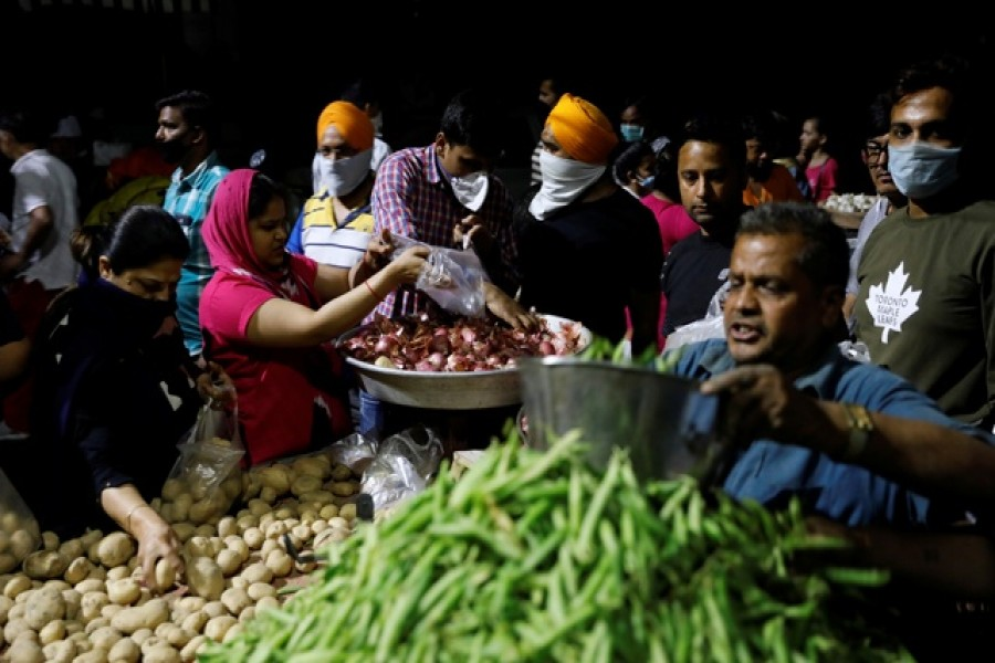 People buy vegetables at a market after India's prime minister Narendra Modi called for a nationwide lockdown starting midnight to limit the spreading of coronavirus disease (COVID-19), in New Delhi, India, March 24, 2020. — Reuters