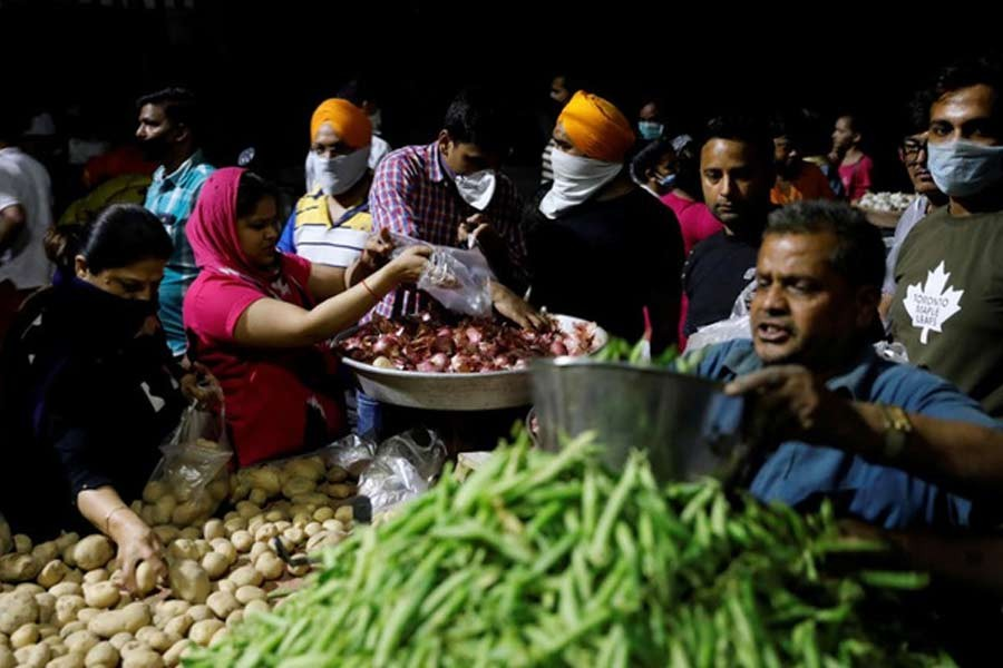 People buying vegetables at a market in New Delhi after Indian Prime Minister Narendra Modi called for a nationwide lockdown starting Tuesday midnight to limit the spreading of coronavirus disease (COVID-19). –Reuters Photo