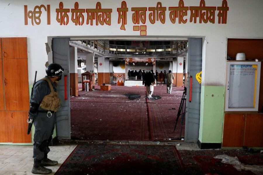 An Afghan policeman inspects inside a Sikh religious complex after an attack in Kabul, Afghanistan on March 25, 2020