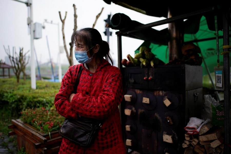 Li Yu, 55, a pedlar selling corn, wears a face mask at an ancient city wall in Jingzhou, after the tourist attraction reopened as the lockdown was eased in Hubei province, the epicentre of China's coronavirus disease (COVID-19) outbreak, March 26, 2020. REUTERS/Aly Song