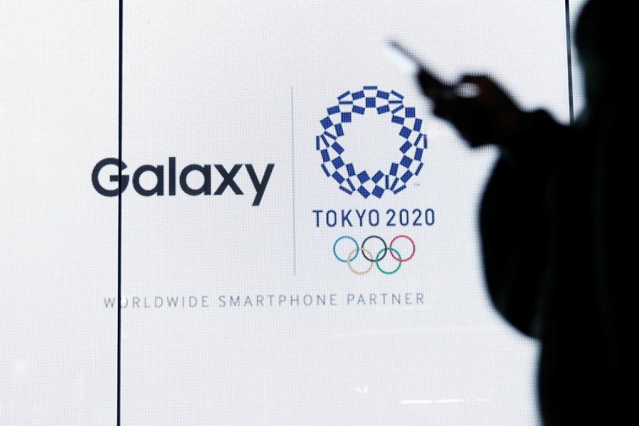 A woman uses her smartphone as an electric screen displaying logos of Tokyo 2020 Olympic Games and Galaxy, a brand name of mobile computing devices by Samsung Electronics and worldwide smartphone partner for the Games, at Galaxy Harajuku in Tokyo, Japan, March 26, 2020. — Reuters