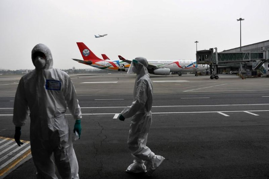 Customs officers in protective suits are seen near a Sichuan Airlines aircraft on the tarmac of Chengdu Shuangliu International Airport following a global outbreak of the coronavirus disease (COVID-19), in Chengdu, Sichuan province, China on March 26, 2020 — cnsphoto via REUTERS