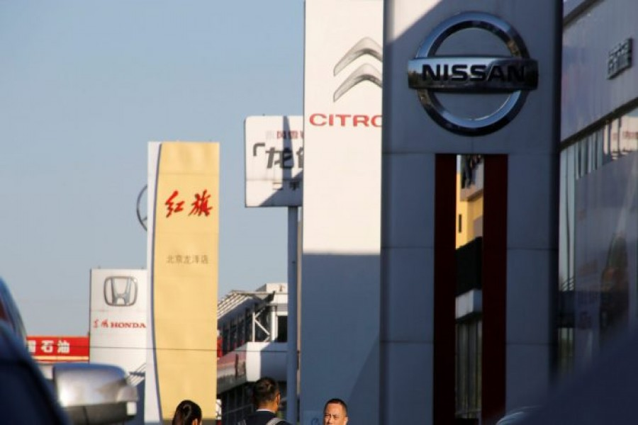FILE PHOTO: People walk near the showrooms of Chinese and foreign car dealerships in Beijing, China, Oct. 11, 2018. REUTERS/Thomas Peter