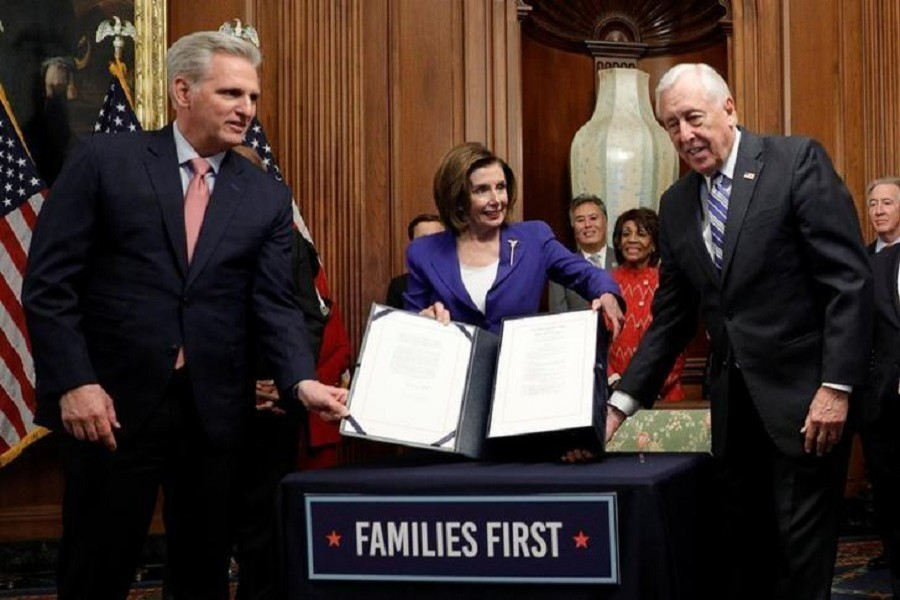 US House speaker Nancy Pelosi (D-CA) is flanked by House minority leader Kevin McCarthy (R-CA) and majority leader Steny Hoyer (D-MD) as she displays the $2.2 trillion coronavirus aid bill during a signing ceremony after the House of Representatives approved the rescue package at the US Capitol in Washington, US, March 27, 2020. — Reuters