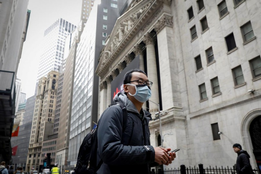 FILE PHOTO: A man wears a mask on Wall St. near the New York Stock Exchange (NYSE) in New York, U.S., March 3, 2020. REUTERS/Brendan McDermid/File Photo