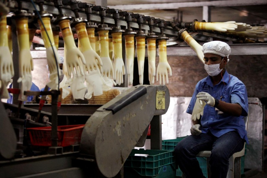 FILE PHOTO: A worker monitors a production line at a Top Glove factory in Meru outside Kuala Lumpur, June 25, 2009. REUTERS/Bazuki Muhammad/File Photo