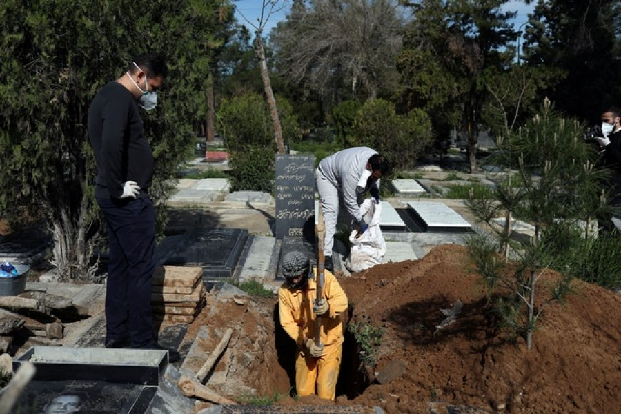 An Iranian man digs a grave to bury the journalist Abdollah Zavieh, who passed away due to coronavirus disease (COVID-19), at Behesht Zahra cemetery in Tehran, Iran, March 24, 2020. WANA (West Asia News Agency)/Ali Khara via REUTERS