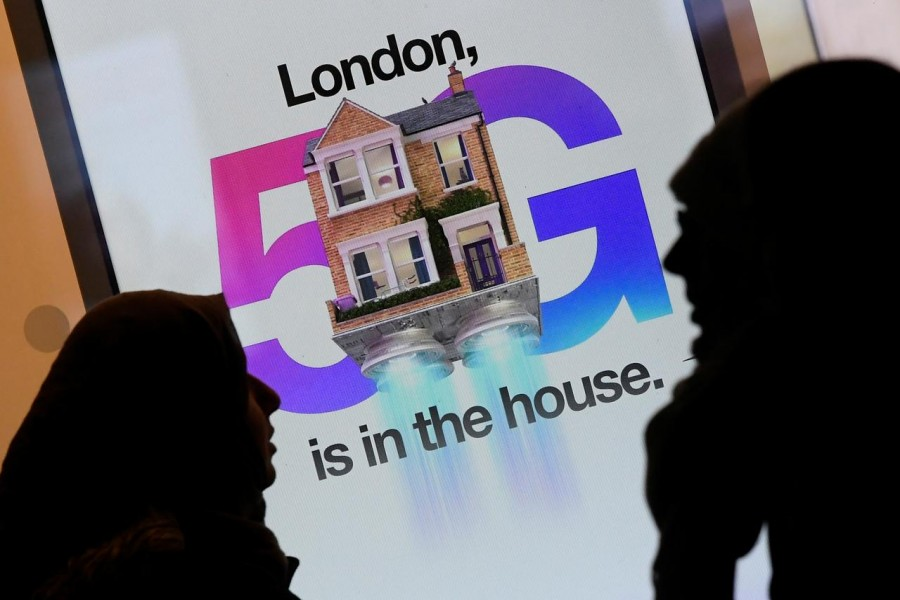 Pedestrians walk past an advertisement promoting the 5G data network at a mobile phone store in London, Britain, January 28, 2020. REUTERS/Toby Melville