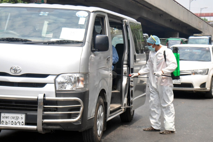 A volunteer in protective suit seen spraying disinfectants inside vehicles on the street near Tejgaon area in Dhaka as a preventive measure against the deadly coronavirus — Focus Bangla/Files
